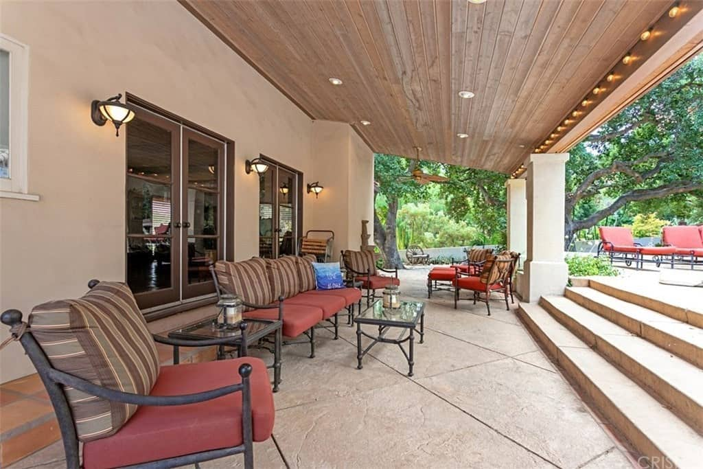 This covered patio features a rectangular coffee table and rustic color sofas. This area is lit by recessed ceiling lights.