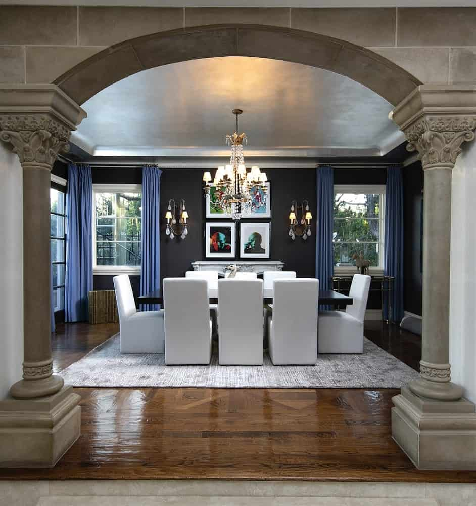 The formal dining room has a charming black rectangular dining table that matches with the black walls. These dark elements are complemented by the white dining chairs, area rug and the framed artworks of the walls.