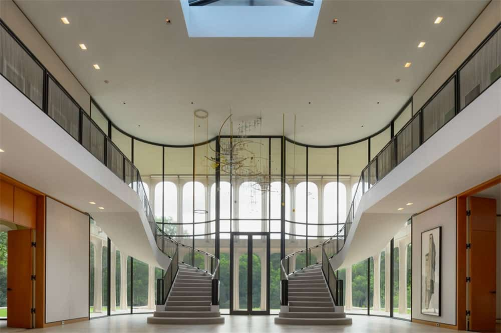 Upon entry of the estate, you are welcomed by this spacious and grand foyer with glass walls accented by the black frames of the glass to stand out against the bright white walls and ceiling with a large skylight in the middle.