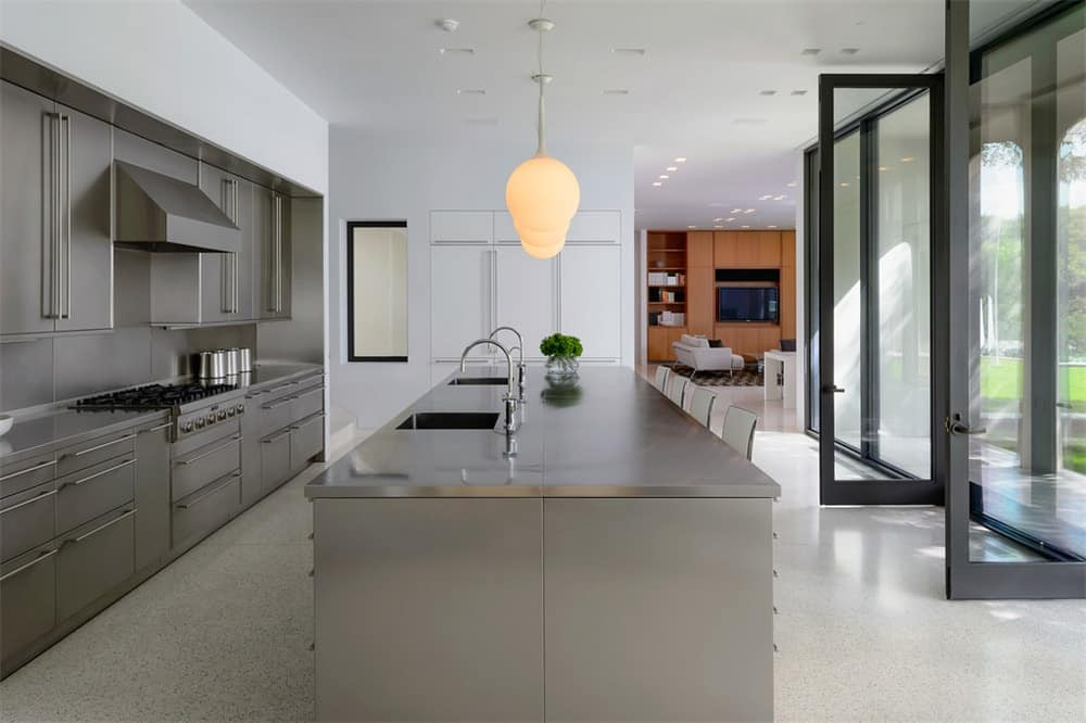 This is the kitchen that has a large kitchen island that houses the faucet across from the cooking area and the breakfast bar topped with a charming pendant light.