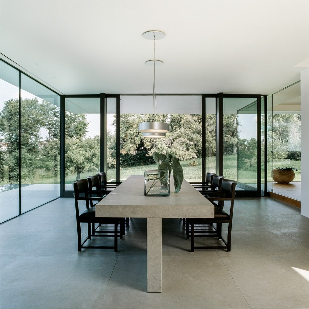This is the gorgeous dining room with glass walls that have black accents on its frames. These pair well with the black chairs surrounding the large rectangular dining table topped with pendant lights from the white ceiling.