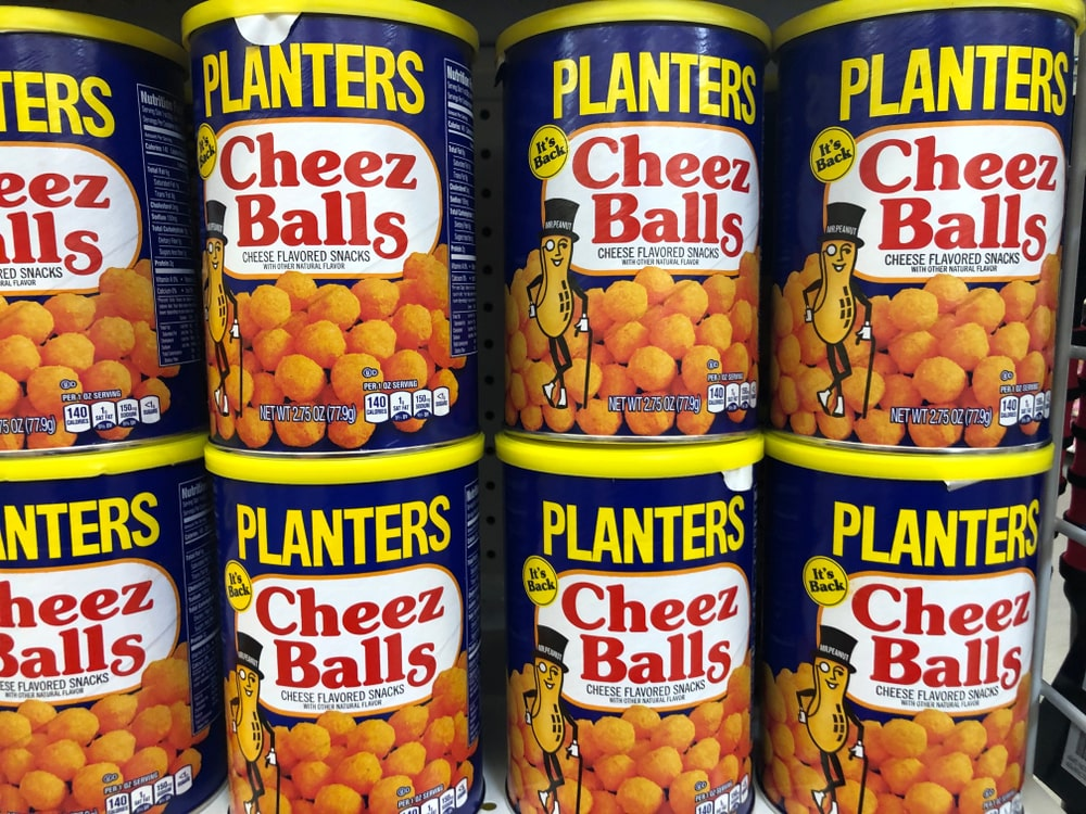 Planters Cheez balls on display on a grocery shelf.