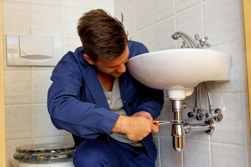 Plumber working at the bathroom sink.