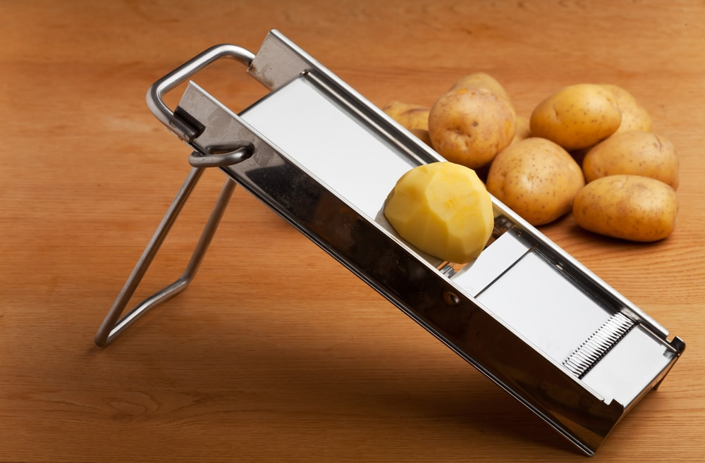 Potatoes and a mandolin slicer on a wooden background.