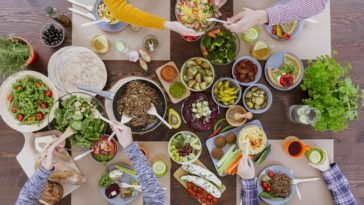 A group of people enjoying a healthy and colorful feast.