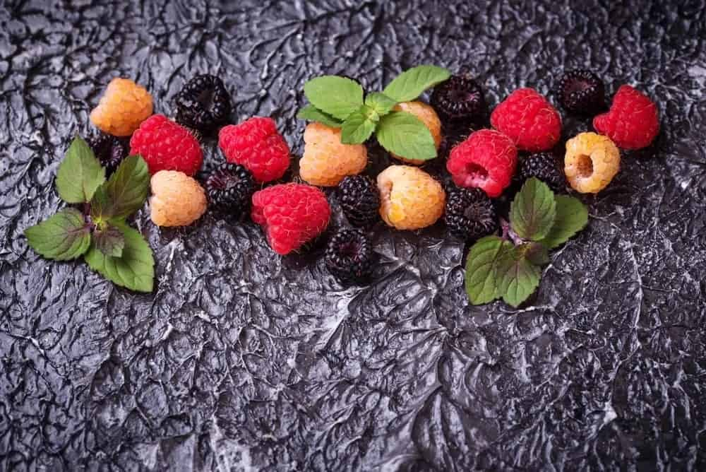 Different types of raspberries on a dark background.