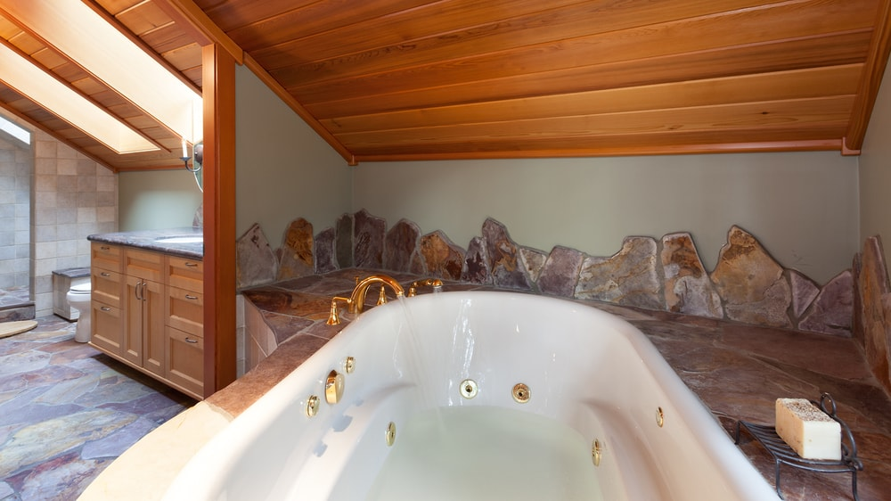 A closer look at the large bathtub by the bed shows that it is in a lovely alcove of wooden shed ceiling and charming mosaic stone that extends to the backsplash. Images courtesy of Toptenrealestatedeals.com.
