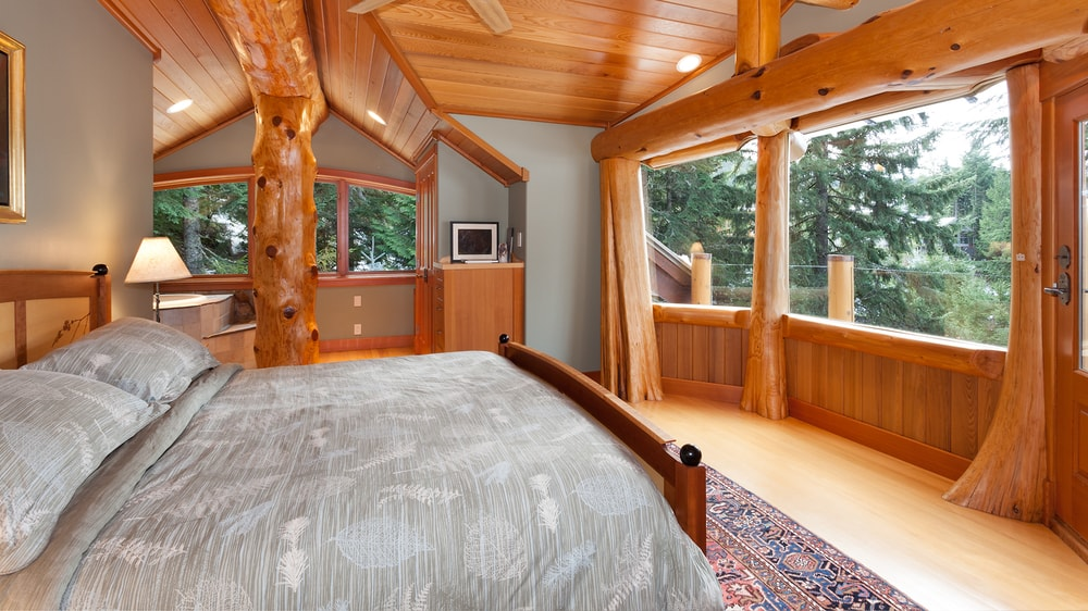 This bedroom has an airy and bright vibe to its large glass windows accented by the log details. This brings in natural lighting as well as a great scenic view for the wooden sleigh bed. Images courtesy of Toptenrealestatedeals.com.