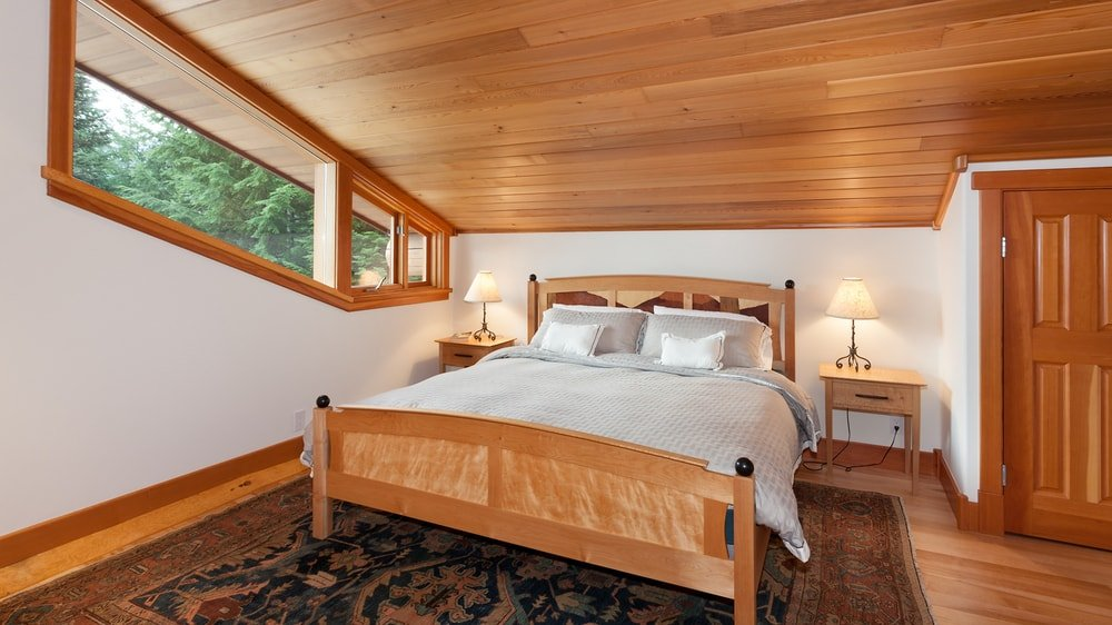This bedroom has a lovely wooden sleigh bed to match the wooden shed ceiling illuminated by its transom windows that follow the lay of the shiplap ceiling. Images courtesy of Toptenrealestatedeals.com.