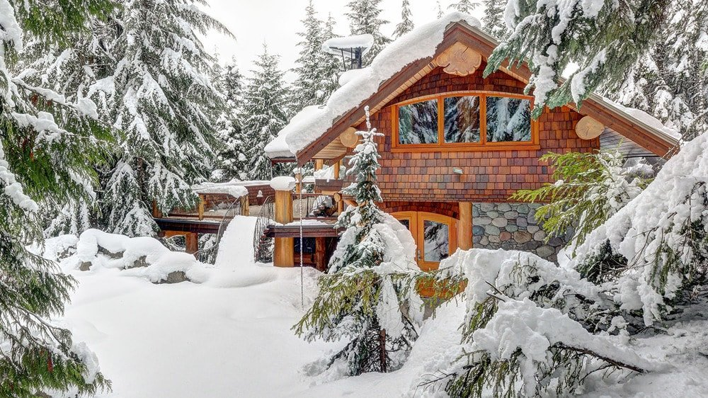 This is the front view of the house where you can see the wooden exteriors of the house standing out against the surrounding blanket of snow of the landscape filled with tall trees. Images courtesy of Toptenrealestatedeals.com.