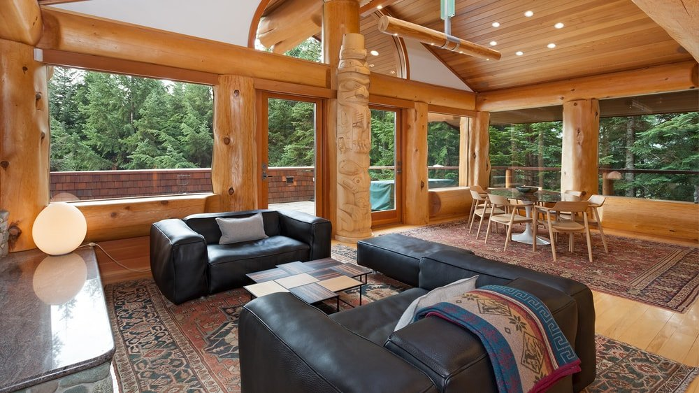 This view of the living room shows its charming tall cathedral wooden ceiling with exposed log beams and a large arched transom glass window to illuminate it. Images courtesy of Toptenrealestatedeals.com.