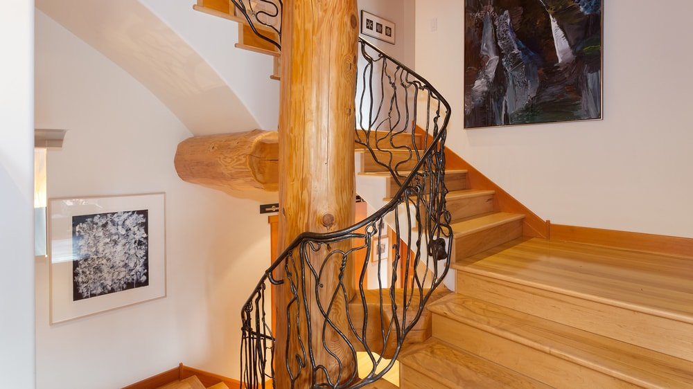 This is a closer look at the charming staircase of the cabin with wooden steps, a large central log pillar and the intricate wrought iron railings that stand out. Images courtesy of Toptenrealestatedeals.com.