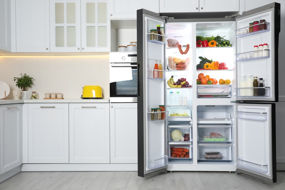 Refrigerator doors wide open in a white kitchen reveal its contents.