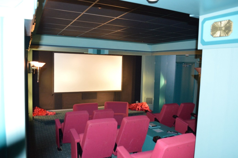 Home theater with a set of stylish pink sectional seats surrounded by blue walls. Images courtesy of Toptenrealestatedeals.com.