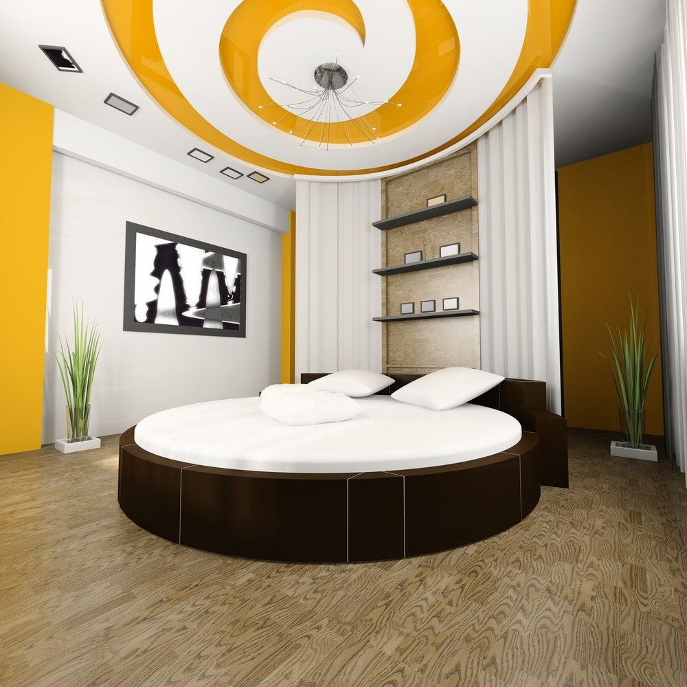 Modern bedroom with a round bed, built-in shelves, and an ornate domed ceiling with stylish lighting.