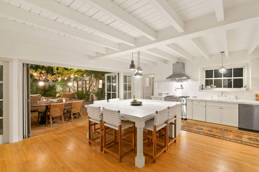 This is a bright and white kitchen with a white beamed ceiling and a large white kitchen island with a built-in table paired with wooden chairs to match the hardwood flooring.