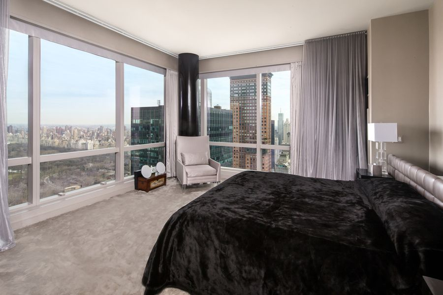 The bedroom suite offers a black bed setup facing the glass walls providing stunning city views. Images courtesy of Toptenrealestatedeals.com.