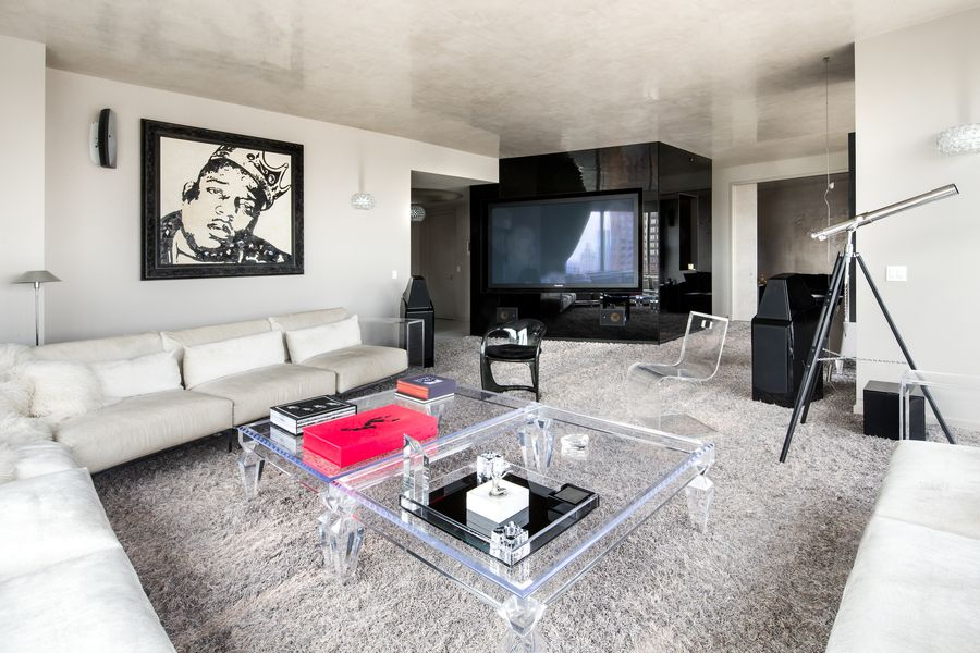 Large living room with a framed Notorious B.I.G. artwork on the wall, along with a large flat-screen TV. Images courtesy of Toptenrealestatedeals.com.