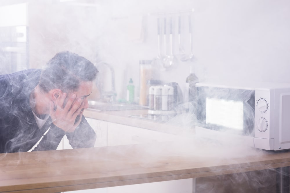 Man looks shocked as he watches smoke coming out of the microwave oven.