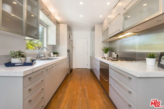 This is a long and narrow kitchen with a light tone to its modern cabinetry that houses the stainless steel appliances. These are then complemented by a rich hardwood flooring and a bright white ceiling with recessed lights.