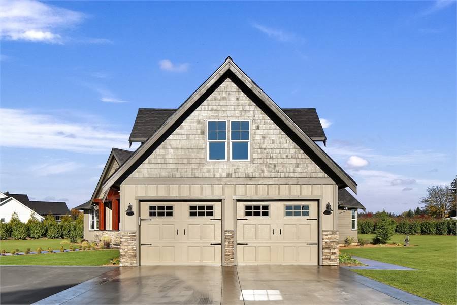 A smooth concrete driveway complements the two-car garage that's accentuated with stone bricks.