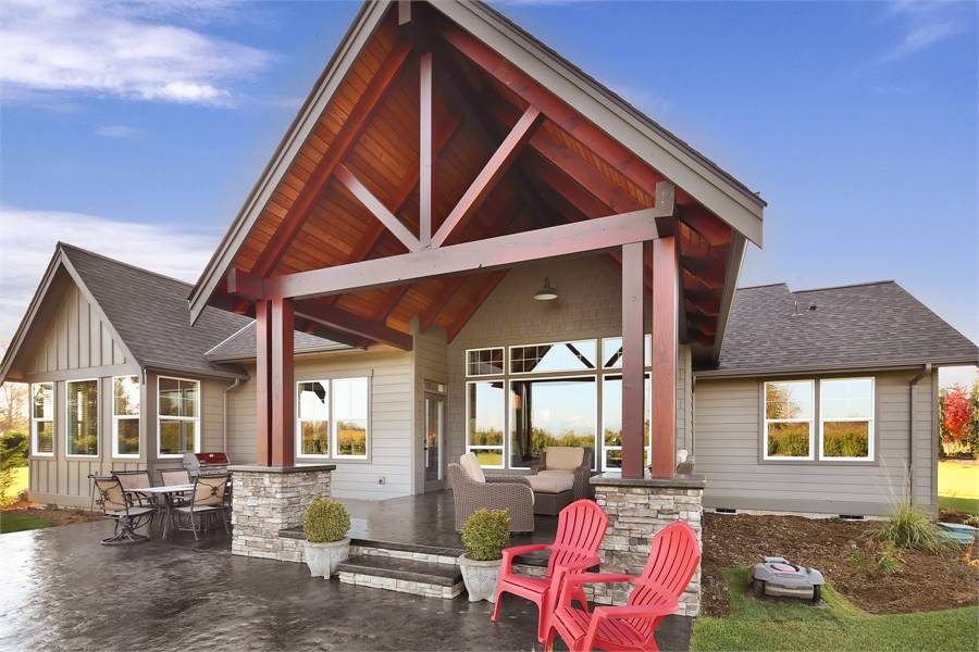 This house features a spacious gabled porch framed with natural wood trims. Stone accents add rich texture to the exterior.