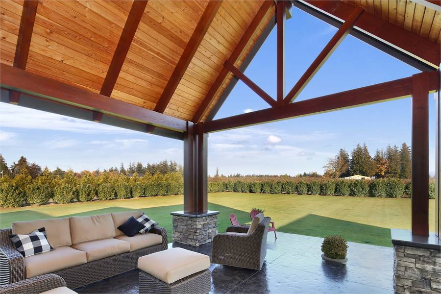 A serene backyard view from the covered patio with tiled flooring and a cathedral ceiling with exposed beams.