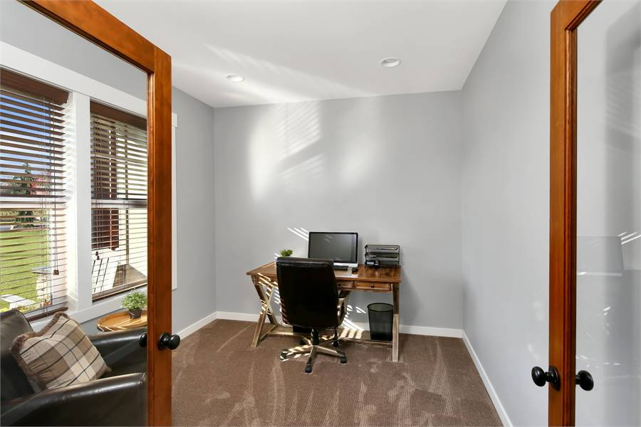 A french door opens to the study with a black leather armchair and a wooden desk paired with a swivel seat.