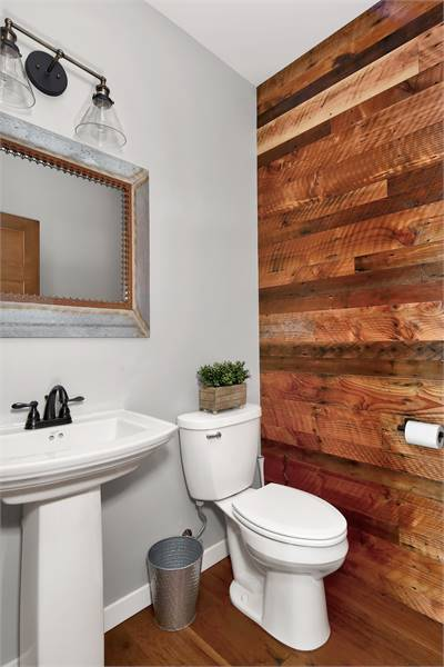 The powder room offers a toilet and a sink pedestal under the rectangular mirror.