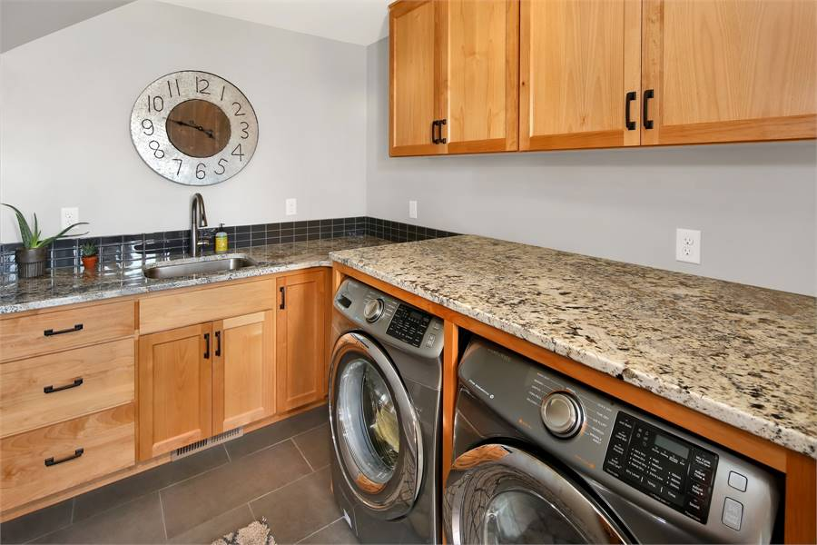 The laundry room is equipped with front-load appliances, wooden cabinets, and an undermount sink paired with a gooseneck faucet.