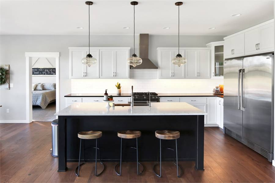The kitchen offers white cabinetry, stainless steel appliances, and a black breakfast island lined with glass pendants and round stool bars.