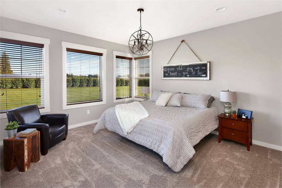 The primary bedroom is furnished with wooden nightstands, a comfy bed, and a black leather armchair paired with a stump side table.