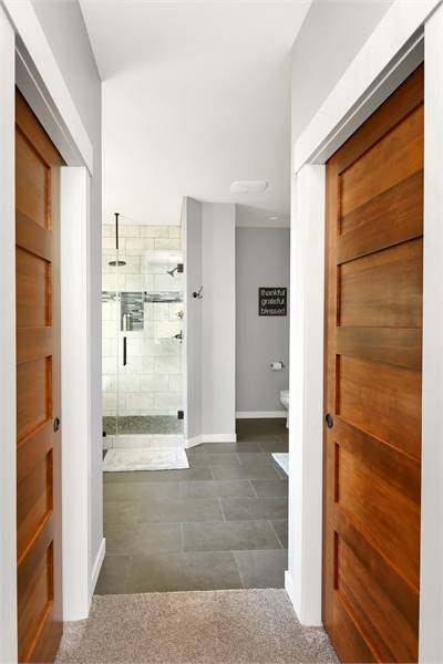 His and her walk-in closets enclosed in wooden doors. It leads to the primary bath with tiled flooring and light gray walls.