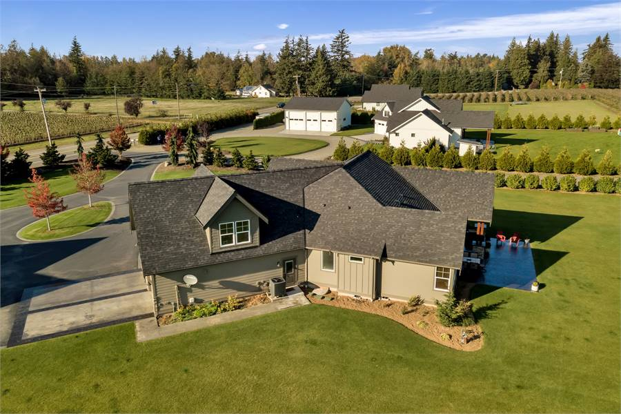 Aerial view of the single-story home showing its varied rooflines, a concrete driveway, and serene landscaping.