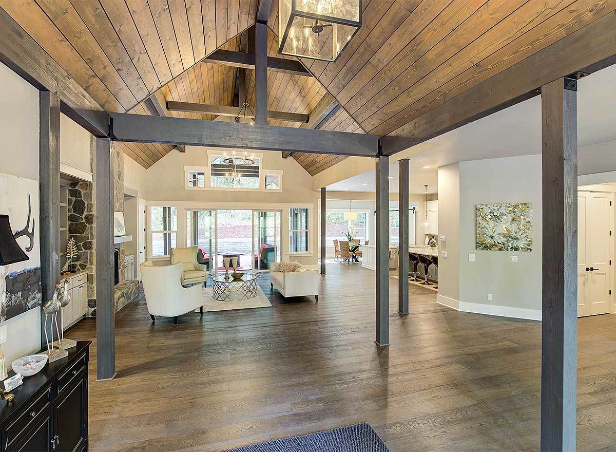 Moving forward is the living room with a cathedral ceiling and dark wood columns.