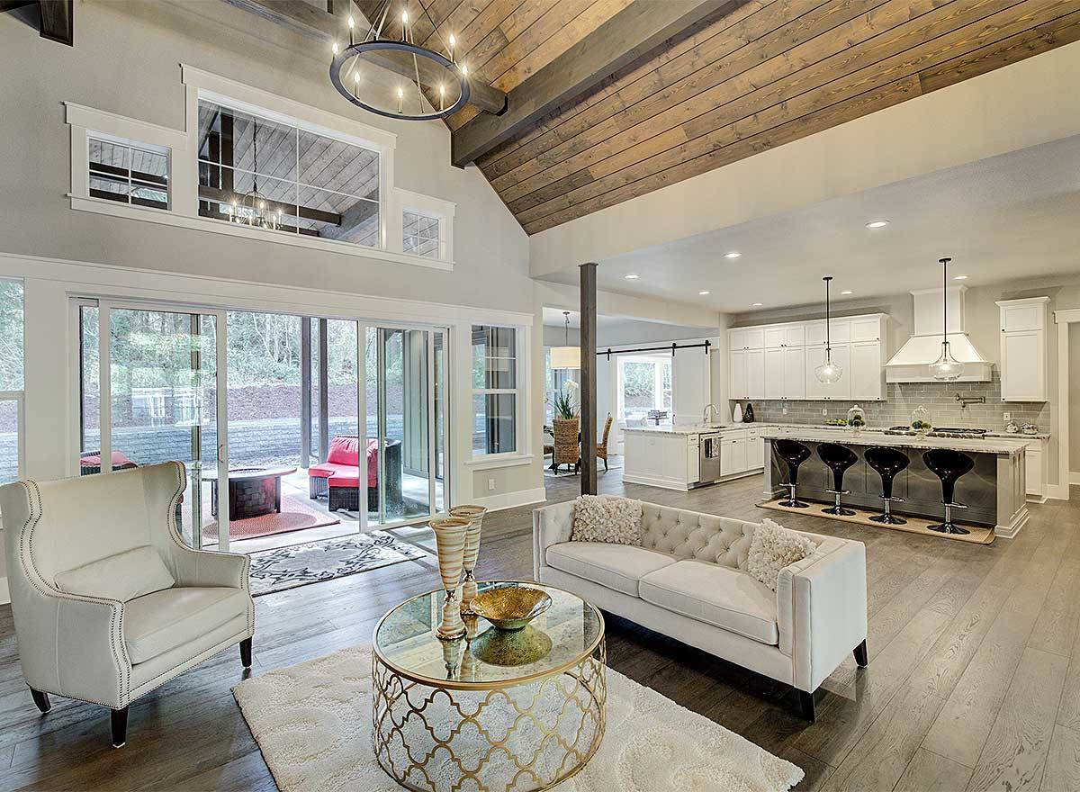 The living room flows into the kitchen and outdoor living accessible via the sliding glass doors.