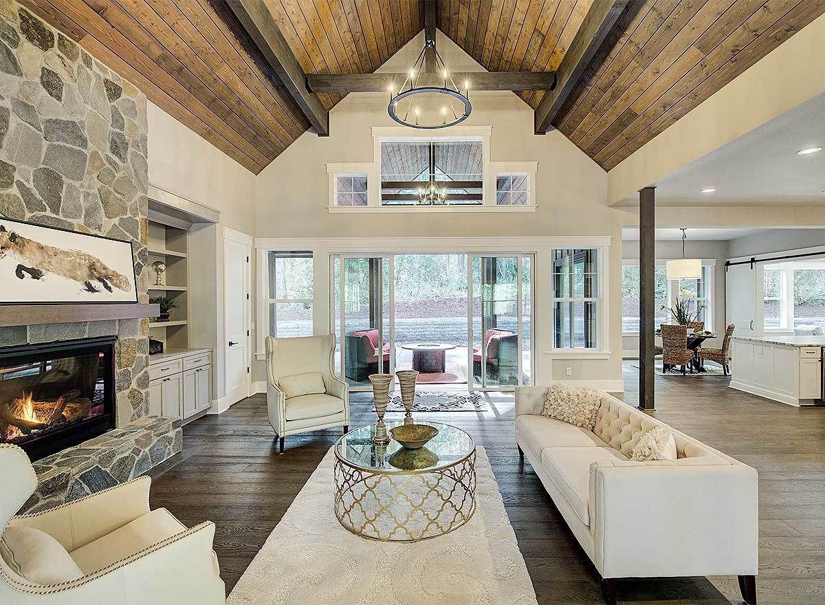 Elegant white seats, a round glass top coffee table, and a stone fireplace complete the living room.