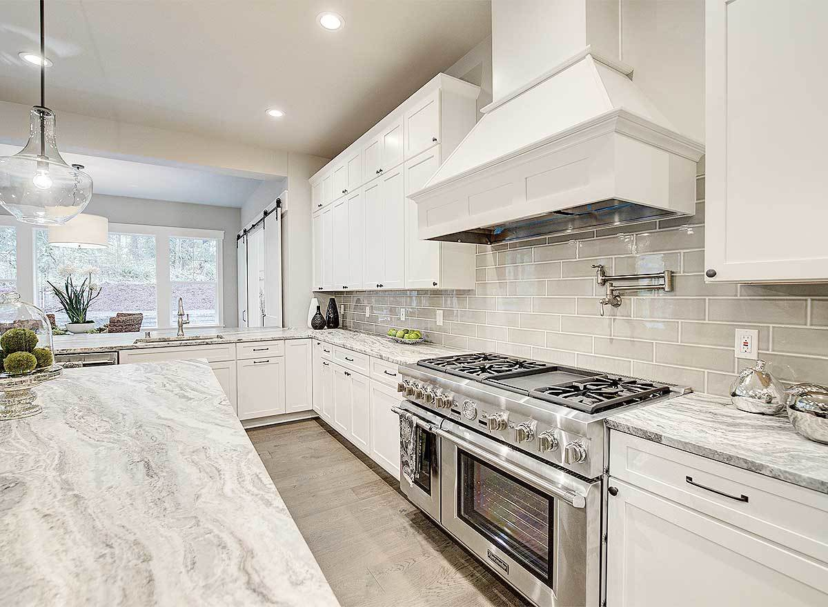 The kitchen is equipped with a center island, stainless steel appliances, and granite countertops fixed against the subway tile backsplash.