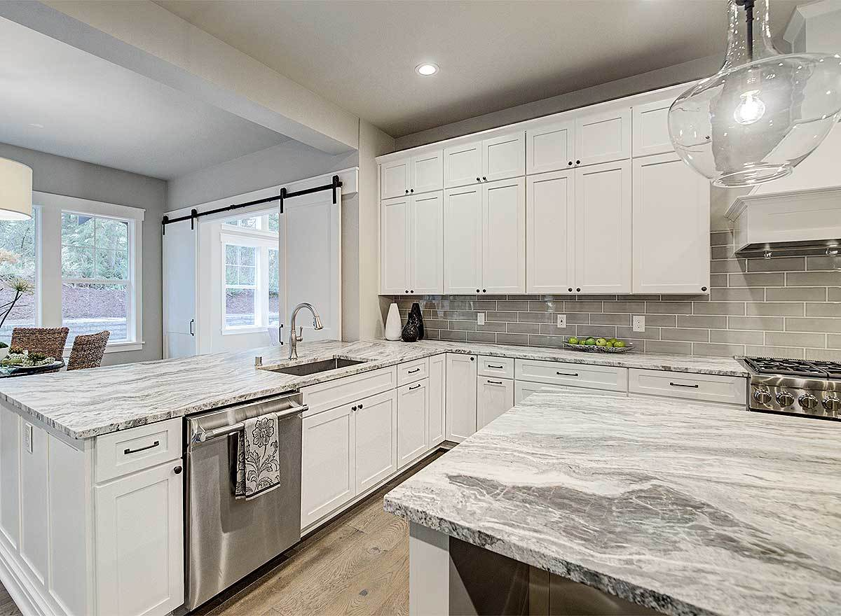An undermount sink is placed on top of the granite counter with white cabinets.