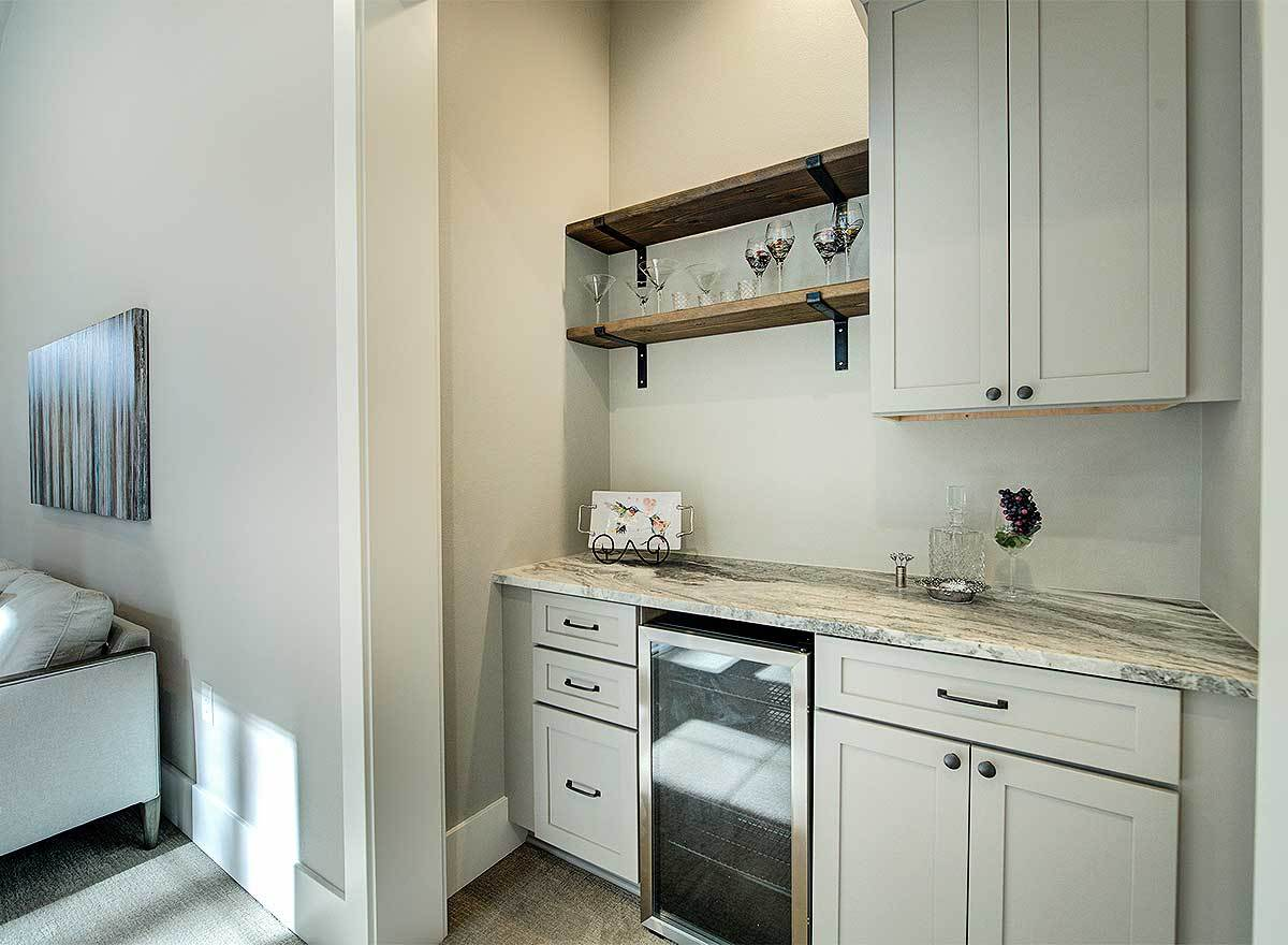 There's a wet bar in the corner filled with gray cabinets, floating shelves, and a wine fridge.