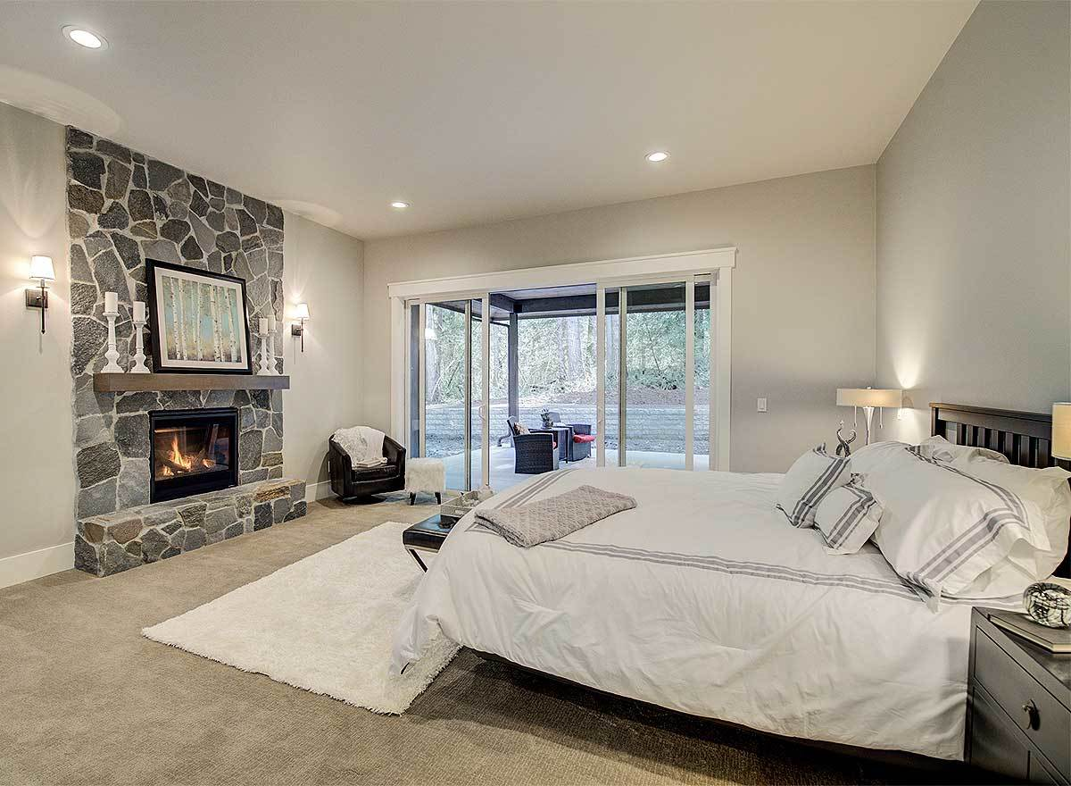 The primary bedroom features a stone fireplace and glass sliders that lead out to the covered patio.