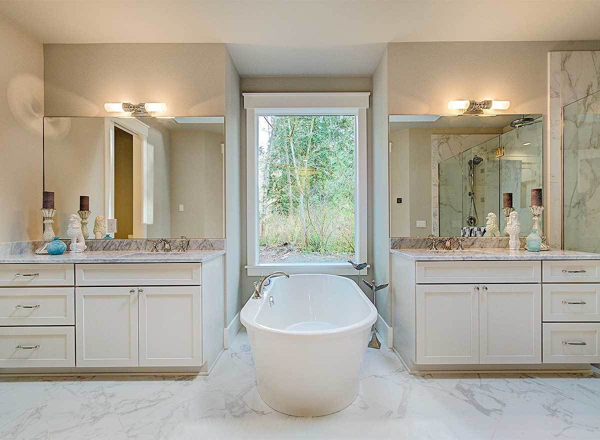 Marble top vanities flank the freestanding tub under the white framed window.