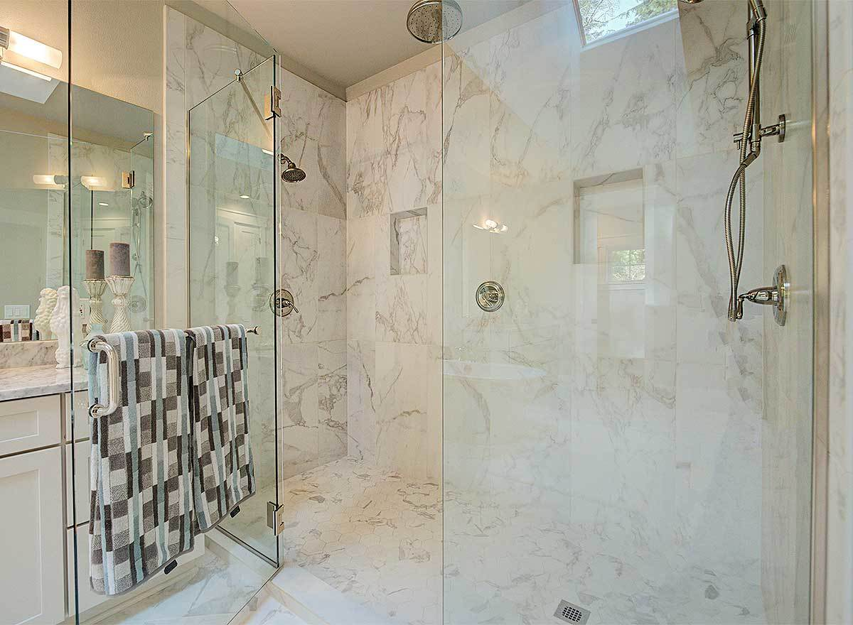 A closer look at the shower shows the inset shelves and chrome fixtures mounted on the marble walls.