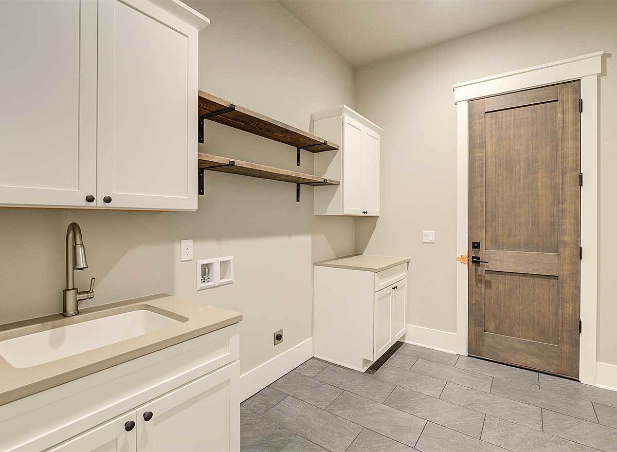 Laundry room with white cabinets, an undermount sink, and wooden shelves that match the hinged door.