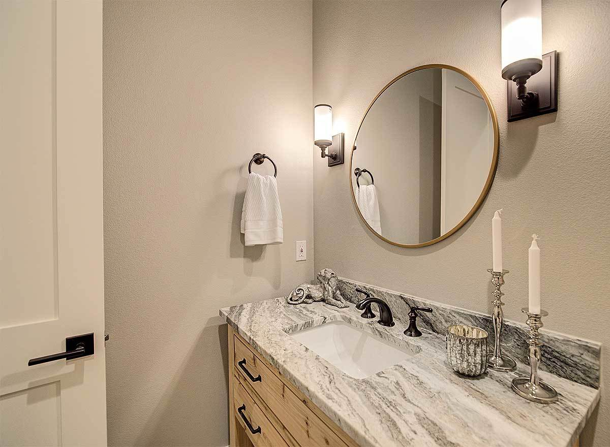 Powder room with sink vanity and a round mirror well-lit by glass sconces.