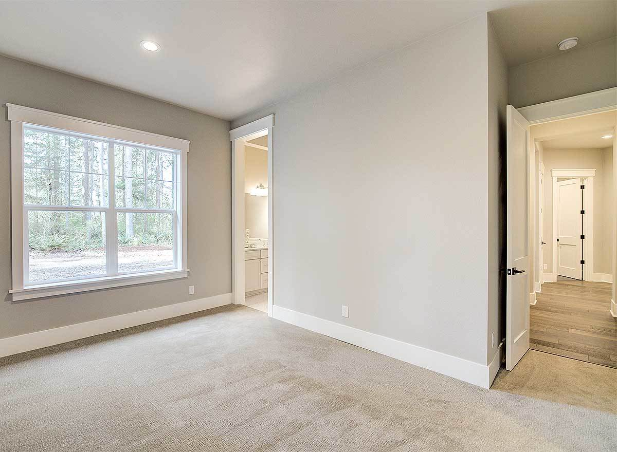 Empty bedroom with light gray walls, carpet flooring, and a white framed window.