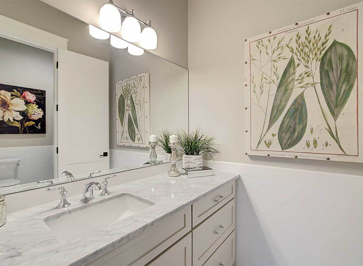 The bathroom offers a sink vanity and toilet reflected in the rectangular frameless mirror.