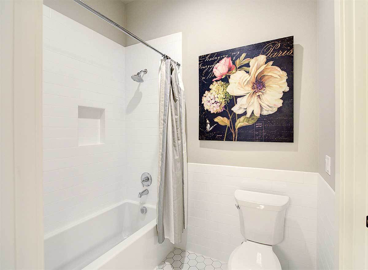 This bathroom has a toilet adorned with a floral artwork along with a shower and tub combo enclosed in gray curtains.
