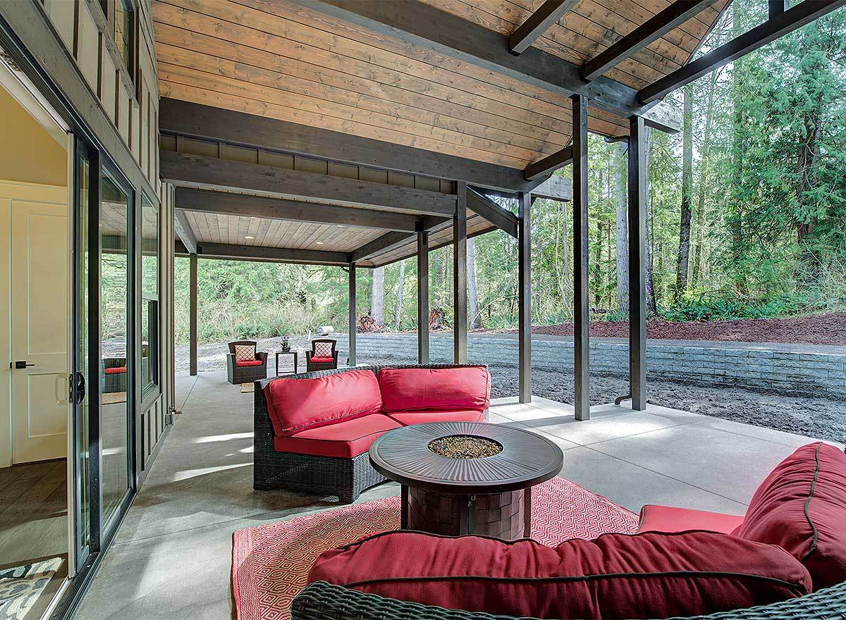 Outdoor living with a round coffee table on top of a red rug surrounded by wicker couches.