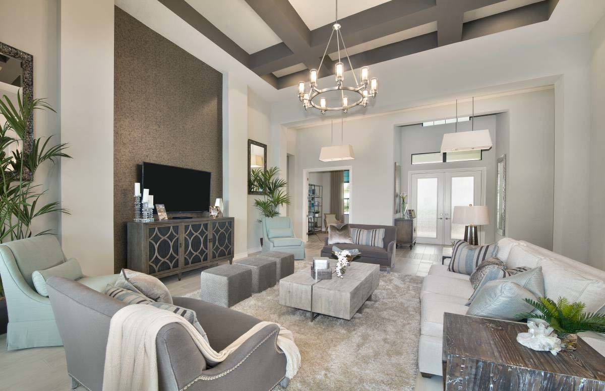 The living room has cozy seats, a sleek coffee table, and a round chandelier hanging from the coffered ceiling.